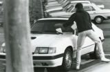 Student removing citation from his car, 1988
