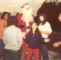 Santa Claus with young people at tree lighting ceremony, 1980